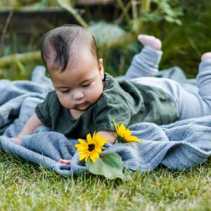Baby mit Babykleidern aus Leinen und Wolle Seide im Sommer