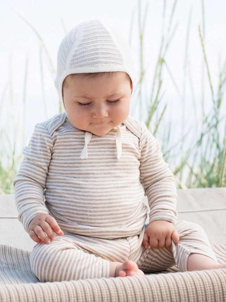 Baby mit Babykleidern im Sommer am Strand