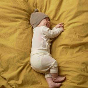 Schlafendes Baby in Body, Baby-Leggins und Baby-Mützchen aus Merino-Wolle