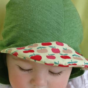 Baby mit Baby-Mützchen aus Bio-Merinowolle und Seide von Glückskind